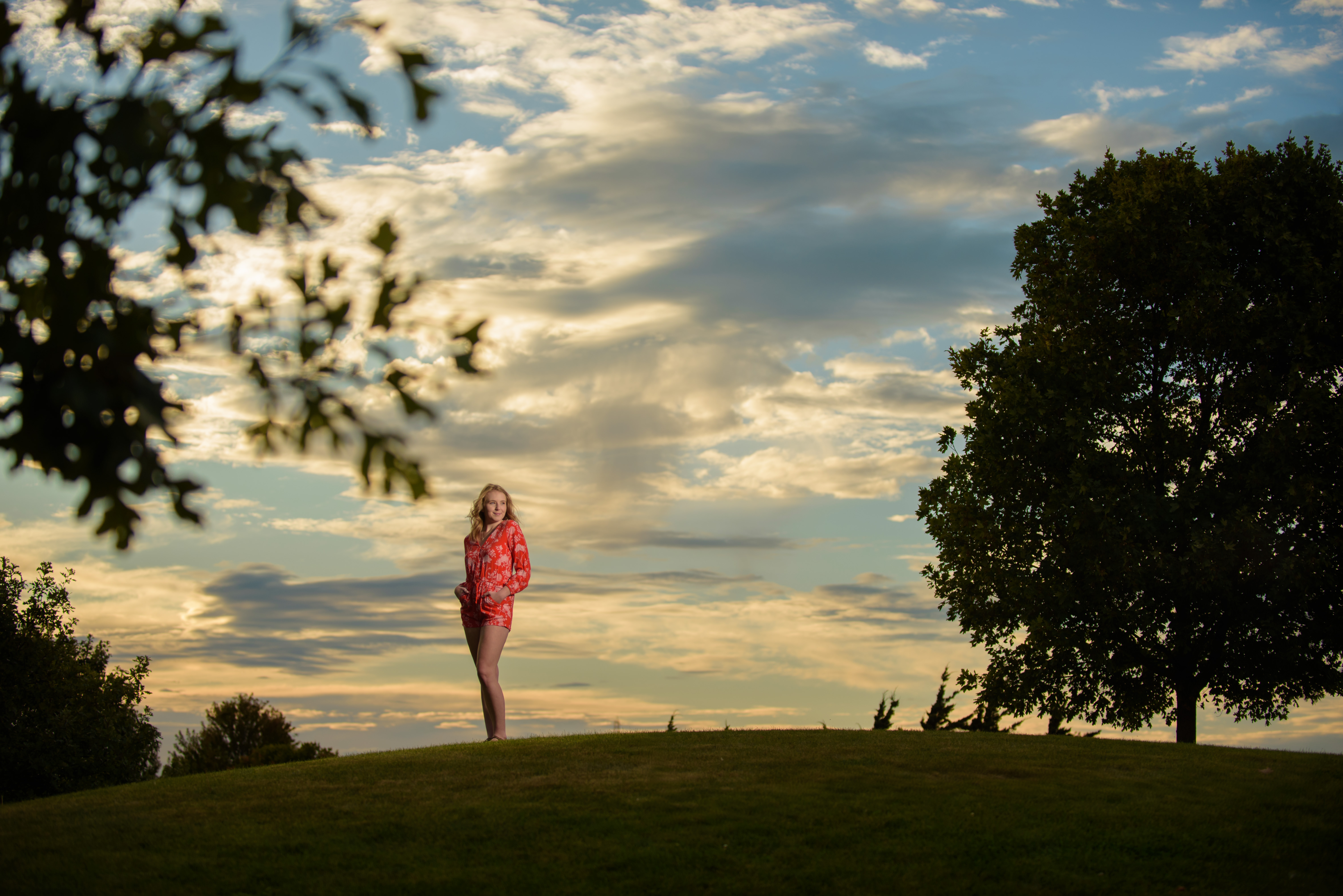 High School Senior Portrait standing on a hill with clouds Independence Grove