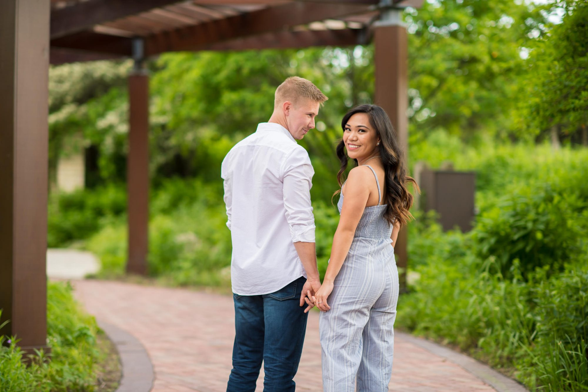 Engaged couple holding hand and looking back at Independence Grove in Libertyville
