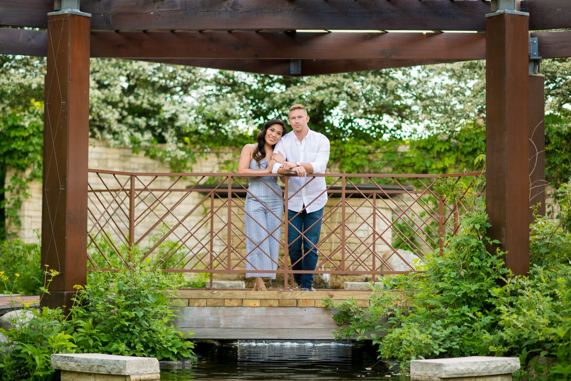 Engaged couple over the bridge at Independence Grove in Libertyville